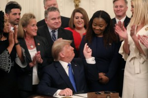 "U.S. President Donald Trump points to human trafficking survivor Bella Hounakey after signing an Executive Order on ""Combating Human Trafficking and Online Child Exploitation in the United States"" at the White House Summit on Human Trafficking in the East Room of the White House in Washington, U.S., January 31, 2020. REUTERS/Leah Millis"